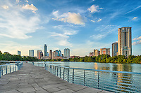 Austin boardwalk along the hike and bike trail which runs along side Ladybird Lake with the city skyline in the background.