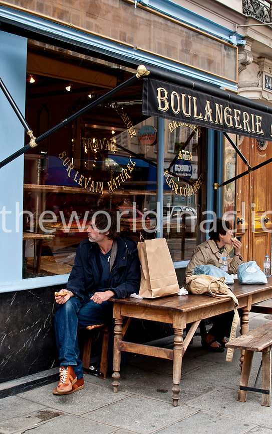 FRANCE, Paris, a man and a woman eating Patisseries outside of Du Pain et des Idees