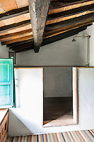 The bathroom  has a rustic simplicity. Traditional local materials were kept during the restoration, such as the terracotta tiles on the ceilings and the original massive wooden beams.