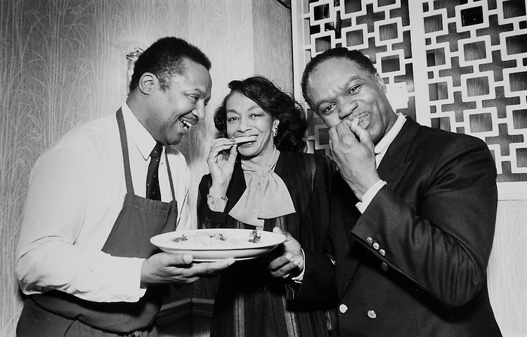 Robert Bush, Rep. Walter E. Fauntroy, D-D.C. with wife Dorothy Simms (Co-owner of Edna's) eating garnish off catfish plate at Surprise Birthday party on January 12, 1990. (Photo by Laura Patterson/CQ Roll Call)