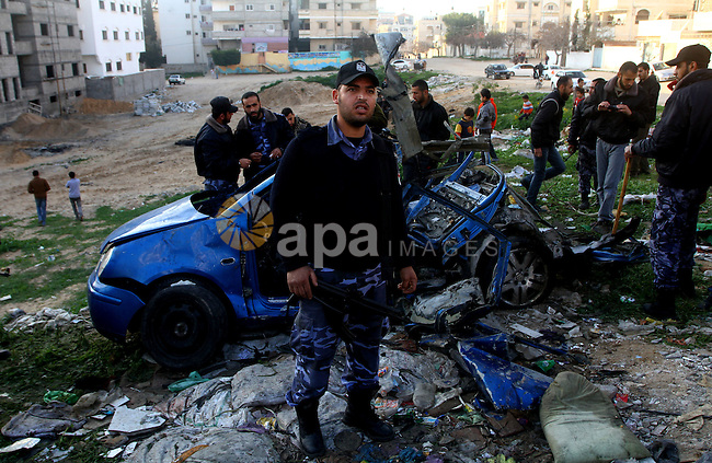 Palestinain policemen inspect the remains of a vehicle after it exploded in Gaza City March 9, 2012. Israel killed the leader of a Palestinian militant faction on Friday in a targeted attack on the car in the Gaza Strip, an Israeli official said. A second man also died in the blast, and a third was injured. The attack came shortly after two rockets were fired at Israel from the coastal territory, causing no damage or injury.Photo by Ashraf Amra