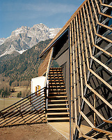 A simple wooden staircase leads to the balcony of this larch wood clad modern chalet overlooked by the snow-capped peaks of the Dolomites