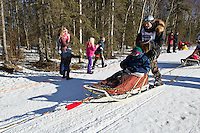 James Lanier and team run past spectators on the bike/ski trail during the Anchorage ceremonial start during the 2014 Iditarod race.<br /> Photo by Britt Coon/IditarodPhotos.com