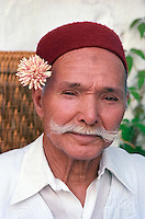 "Tunisia, Sidi Bou Said.  Coffee Shop Owner, Hajj Omar, wearing a Chechia, the Traditional Tunisian Hat, and a Jasmine Sprig behind the Ear.  The grayish spot (""zabiba"") in the upper middle of his forehead is a light callus. This often marks a faithful observer of the Muslim prayers five times a day, in which the forehead gently comes in contact with the prayer rug as the worshipper goes through his prostrations."