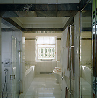 Grey and white marble on the floors and walls have resulted in a bathroom of subtle luxury