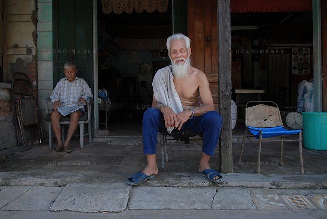 An old man sits outside of a coffee shop and watches street life in Ho Chi Minh City, Vietnam.