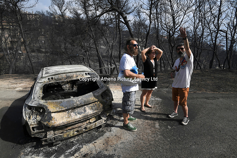Pictured: People asses the damage in the aftermath of the wild forest fires in the Neos Voutzas area near Rafina, Greece. Tuesday 24 July 2018<br /> Re: Deaths caused by wild forest fires throughout Greece.