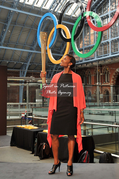 Denise Lewis looks up at the torch as she holds the torch under the Olympic rings. 2012 London Olympic Torch Prototype designed by Edward Barber and Jay Osgerby. St Pancras Station. London. 08/06/2011. MANDATORY Credit Sportinpictures/Garry Bowden - NO UNAUTHORISED USE - 07837 394578
