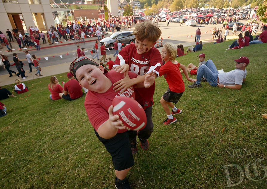 NWA Democrat-Gazette/BEN GOFF @NWABENGOFF<br /> Ethan Ulibarri (from left), 9, of West Monroe, La., Hamilton Needler, 9, of Little Rock, and Liam Osbon, 8, of Huston, Texas play on Saturday Oct. 15, 2016 before the Arkansas football game against Ole Miss at Razorback Stadium in Fayetteville.