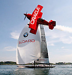 The Oracle Challenger, an aerobatics biplane flown by Sean D. Tucker, flies over the USA-76 BMW ORACLE Racing America's Cup yacht, Wednesday, June 16, 2004, in the waters off Newport, R.I. BMW ORACLE Racing is to compete for the UBS Trophy against current America's Cup champion Team Alinghi. The Oracle biplane is in town for the Rhode Island National Guard Airshow. Both events start this weekend. (AP Photo/Victoria Arocho)