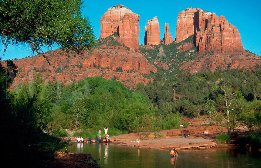 Scenic of red rock formations with a few people enjoying the water below at Red Rock Crossing State Park. Sedona, Arizona.