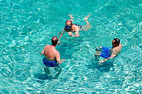 Swimmers in the crystal clear sea water at an isolated cove beach at Riserva Naturale dello Zingaro [ Zingaro nature reserve ] Scopello, Castellammare Del Golfo , Sicily.