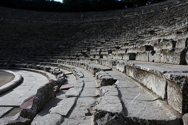 EPIDAURUS, GREECE - APRIL 15 : A low angle view of the seating in the Cavea of the Theatre, on April 15, 2007 in Epidaurus, Greece. The Theatre, designed by Polykleitos the Younger, was built in the late 4th century BC and extended in the Hellenistic period. It was rediscovered in 1881 and significantly restored in the 1950s.  It has the three main features of a Greek theatre: the orchestra, the skene and the cavea, a raked semi-circular auditorium with radiating diazomas. Between the cavea and the orchestra is a paved drainage depression. The theatre is renowned for its accoustics thanks to the symmetry of the cavea, seen here half in shadow from the early morning light. (Photo by Manuel Cohen)