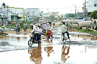 Motorbike traffic weaves between huge water-filled potholes in the road. Large concrete pipes by the side of the road promise a future solution to the problem of flooding in the area. Tay Ninh, Vietnam