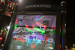 Neon signs reflected in the glass on an Information Directory on Hollywood Boulevard, Hollywood, Los Angeles, CA