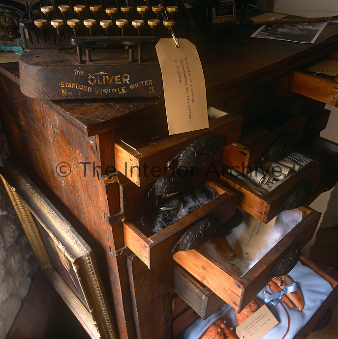 An eclectic mix of objects are stored in a wooden chest with drawers open. An old typewriter sits on top.