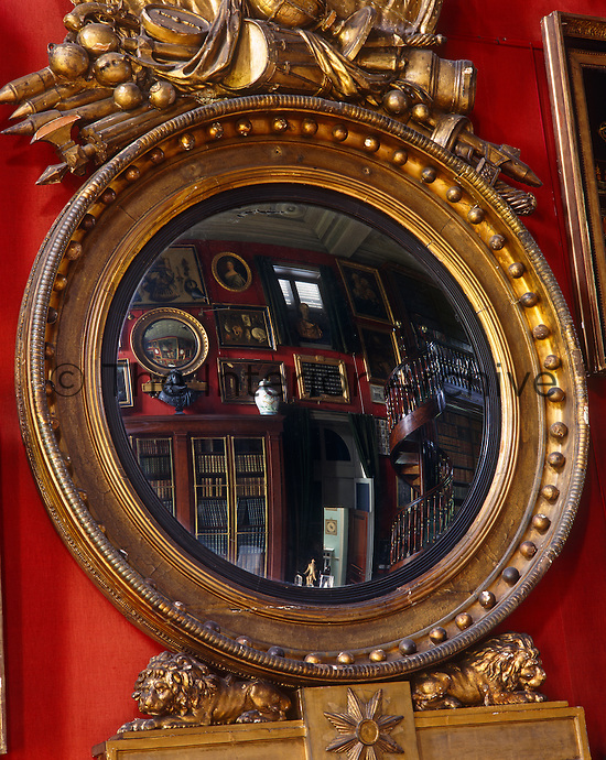 The spiral staircase of the double-height library is reflected in this gilt-framed convex mirror
