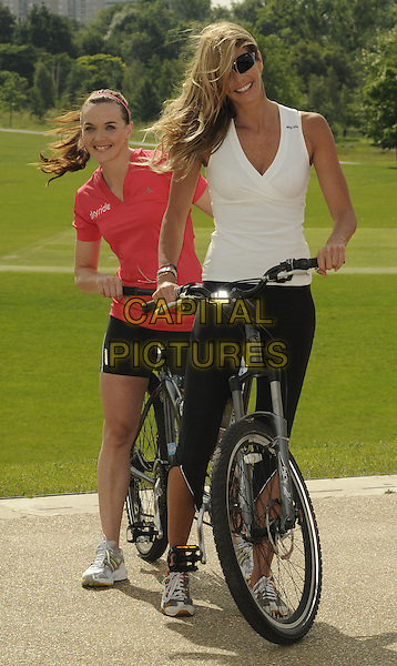 VICTORIA PENDLETON & ELLE MacPHERSON .Launch of Skyride - Sky's campaign to get people back on their bikes through a summer of free cycling events, Regents Park, London, England. .June 17th, 2009 .full length tandem bike bicycle red white black spandex shorts top sunglasses shades.CAP/CAN.©Can Nguyen/Capital Pictures.