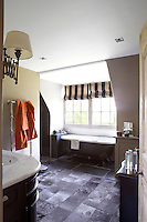 The floor of the comfortable guest bathroom is covered with warm leather tiles and the bath is situated in an alcove underneath the window