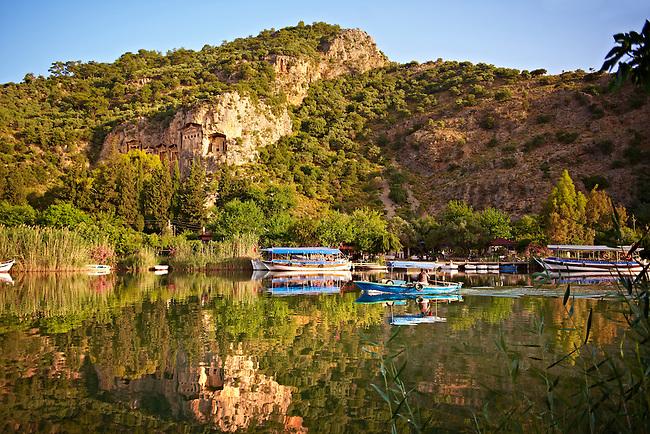 Boats on Dalyan Çay River with Lycian Rock Tombs in the cliffs . Mediterranean coast Turkey