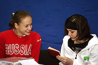 Marina Shpekt of Russia and Anna Bessonova of Ukraine (Anna studies Marina's passport) smile while completing press information forms before 2006 Deriugina Cup Grand Prix event at Kiev, Ukraine on March 16, 2006. (Photo by Tom Theobald)