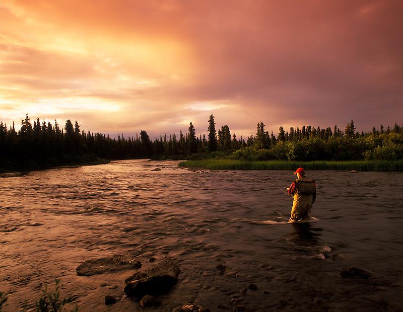 Fly fisherman on Gulkana River at sunset, Alaska
