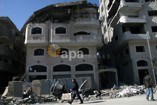 Hamas policemen walk past a destroyed Hamas-run Interior Ministry in Gaza February 28, 2008, after it was bombed by Israeli military aircraft. Israeli Prime Minister Ehud Olmert vowed Thursday to make Hamas militants pay a heavy price for rocket attacks despite US concerns about civilians in the Gaza Strip.