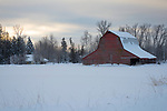 Idaho, North, Bonner County, Sandpoint. A rural farm scene with red barn in a winter landscape at dawn.