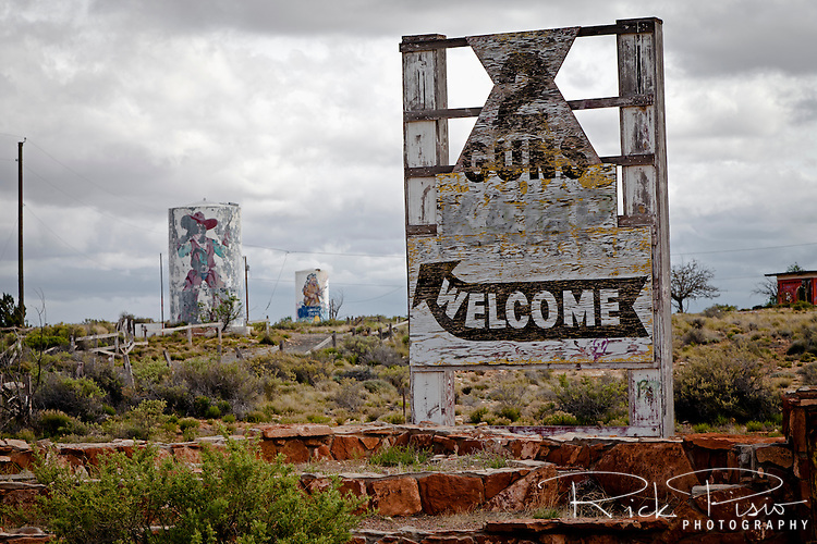 "2 Guns Kampground Entrance. Two Guns is located in Arizona, east of Flagstaff, on what was formerly Route 66. Two Guns was originally called ""Canyon Lodge"" when the National Trail Highway moved westward. Later, the National Trail was re-named Route 66, the site's name was changed to Two Guns, because the proprietor of the facilities located there was one Henry E. Miller, who called himself ""Two Gun Miller."" During the heyday of Route 66, Two Guns became one of the numerous tourist traps along the way, with a gas station, overnighting accommodations, a food emporium, as well as a zoo. Two Guns went into decline with the building of the Interstate."