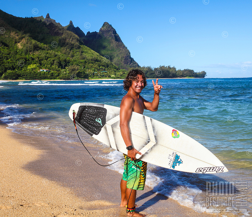 A surfer gives the peace sign at Tunnels Beach, with Makana Mountain in the distance, Kaua'i.