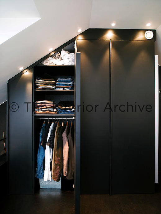 Floor-to-ceiling wardrobes in the bedroom are lit by recessed ceiling lights