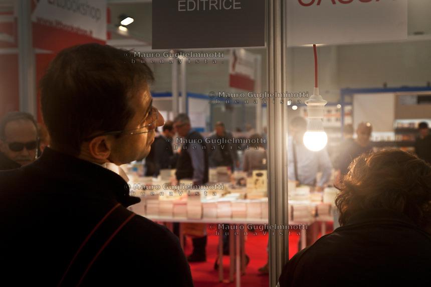 Italia Torino Salone del libro 2014  un uomo guarda un banco di libri illuminato  da una lampadina