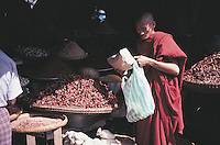 The russet of a monk's robes is perfectly matched to the colours of a dried goods stall in Pegu, Burma.