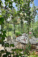 A corner of a garden room with a glass roof and walls allowing a view of the garden beyond. A trailing ivy hangs above a garden table and chairs.