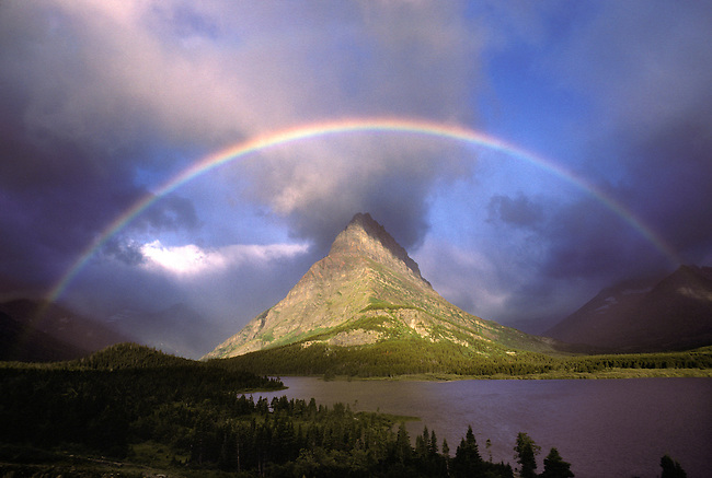 Full rainbow and stormy sky over Grinnell Point and Swift Current Lake in Glacier National Park, Montana.