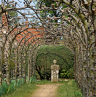 A weathered stone statue stands out against the clipped hedge at the end of this arbour