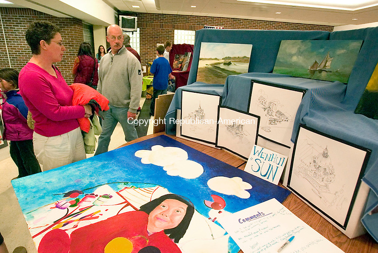 SOUTHBURY, CT--27 APRIL 2007--042707JS15-Pam Riel and her husband Jim Riel looks over some of the artwork by Advanced Placement art student Wenhui Sun during the Regional 15 School District's 19th annual Gallery Opening of Selected Student Artwork Friday at Pomperaug High School in Southbury. <br /> Jim Shannon / Republican-American
