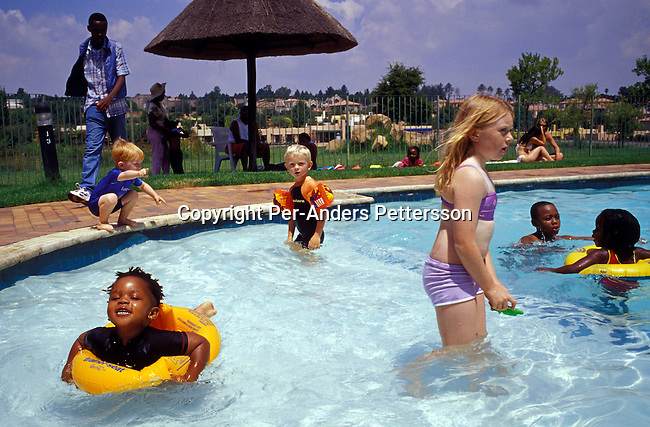 JOHANNESBURG, SOUTH AFRICA - FEBRUARY 29: Lebone Dube, age 4 (far right), playing in a swimming pool with her friends at her birthday party on February 29, 2004 in Cedar Lake, a up-market gated community in Johannesburg, South Africa Her father, Oscar Dube, works as a Key Account manager for the Swedish mobile phone equipment maker Ericsson and his wife, Mpho Dube, is fund manager at Old Mutual, an insurance company in SA. They belong to the new black elite in SA. Lebone attends an exclusive pre-school with mostly white children and she invited them for her birthday party. Well educated and connected, they have risen from the poverty in the townships to a very different lifestyle, since the fall of Apartheid and the start of democracy in the country in 1994. .Photo: Per-Anders Pettersson/iAfrika Photos....