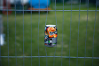 "Drinks can stuck in the wire fencing at ""Showtime"", part of the London 2012 Festival of Arts to celebrate the London Olympics.  A family fun spectacle including dance, painting, music, acrobatics and some large mobile dynosaurs walking amongst the crowd.  On Blackheath Common, Saturday August 4th and funded by the Mayor of London and Arts Council England."