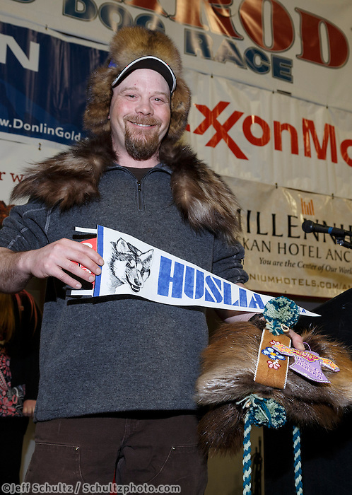 Aaron Burmeister shows off his native-made gifts from the villagers of Huslia for being the first musher to their half-way checkpoint at the finishers banquet in Nome on Sunday  March 22, 2015 during Iditarod 2015.  <br /> <br /> (C) Jeff Schultz/SchultzPhoto.com - ALL RIGHTS RESERVED<br />  DUPLICATION  PROHIBITED  WITHOUT  PERMISSION