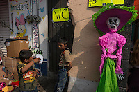 "Boys playing next to a female skeleton in the market on Day of the Dead celebrations in Mixquic. Mexicans visiting their dead relatives, lighting candles, lighting incense and decorating their graves for the Day of the Dead festival in San Andres Mixquic shot as part of the Sony RX100 III ""Celebrate The Streets"" series."