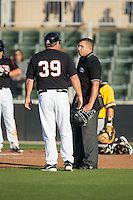 Kannapolis Intimidators manager Tommy Thompson (39) has a discussion with home plate umpire Jonathan Parra during the game against the West Virginia Power at CMC-Northeast Stadium on April 21, 2015 in Kannapolis, North Carolina.  The Power defeated the Intimidators 5-3 in game one of a double-header.  (Brian Westerholt/Four Seam Images)