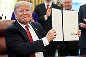 """United States President Donald J. Trump holds a signed Executive Order to strengthen the Trump Administration's """"Buy American"""" policy by encouraging recipients of Federal financial assistance for infrastructure to """"Buy American"""" in the Oval Office of the White House on January 31, 2019 in Washington, DC. <br /> Credit: Oliver Contreras / Pool via CNP"""