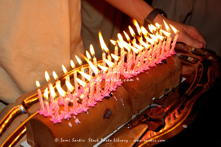 Man carrying a chocolate cake heavily laden with forty lit birthday candles.