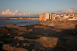 Rocky coastline at dusk looking north from town ramparts towards modern apartment buildings, Essaouira, Morocco