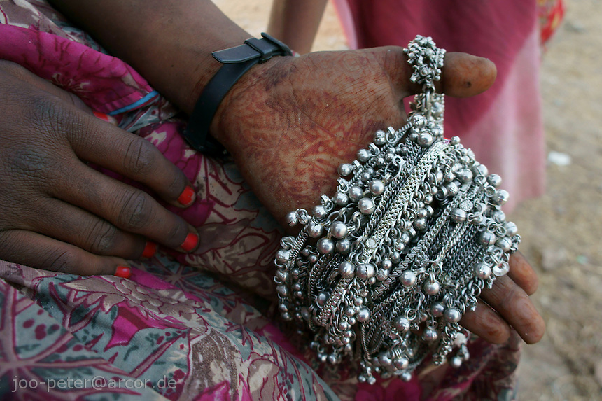 hands of a girl with henna tatoo selling jewlery