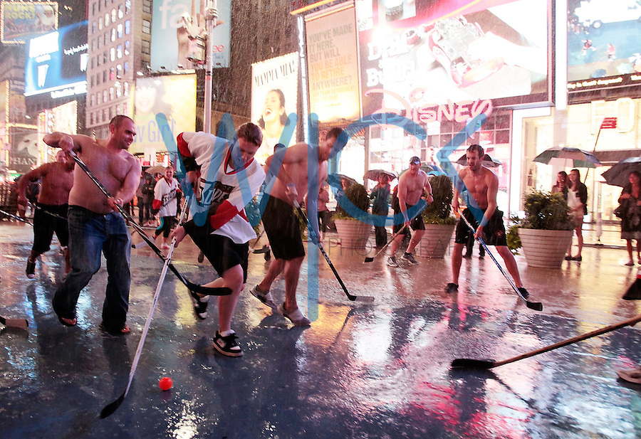 NEW YORK - AUGUST 27:  Members of the Vancouver Fire Department play a friendly game of hockey in Times Square in the pouring rain as Hurricane Irene makes it way towards the city on August 27, 2011 in New York, New York.  (Photo by Jared Wickerham/Getty Images)