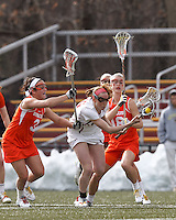 Boston College defender Claire Blohm (26) works to clear ball.  Syracuse University (orange) defeated Boston College (white), 17-12, on the Newton Campus Lacrosse Field at Boston College, on March 27, 2013.