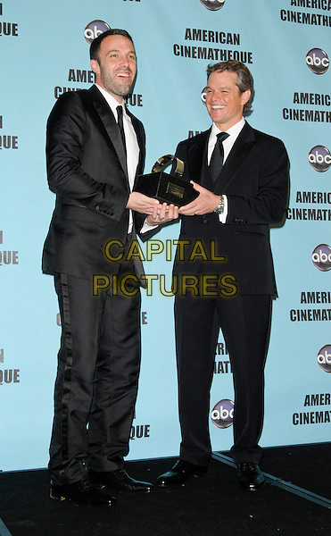 BEN AFFLECK & MATT DAMON .at the 24th Annual American Cinematheque Awards at the Beverly Hilton Hotel in Beverly Hills, California, USA, March 27th, 2010.  .full length black suit tie white shirt award trophy winner holding winners smiling laughing funny .CAP/ROT.©Lee Roth/Capital Pictures.