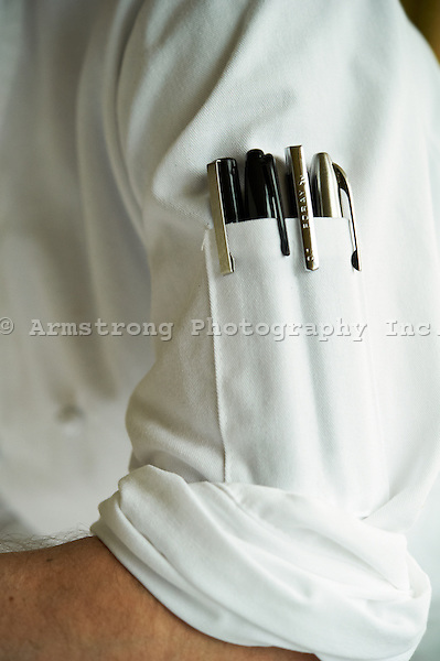 Close up of the arm of a man in a chef's coat with pens in the arm pocket